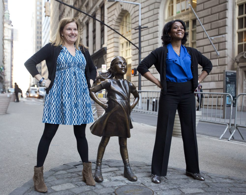"Two women pose with the ""Fearless Girl ""statue on Wall Street in New York last March. (Mark Lennihan/AP)"