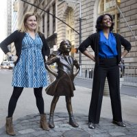 """Two women pose with the """"Fearless Girl """"statue on Wall Street in New York last March. (Mark Lennihan/AP)"""