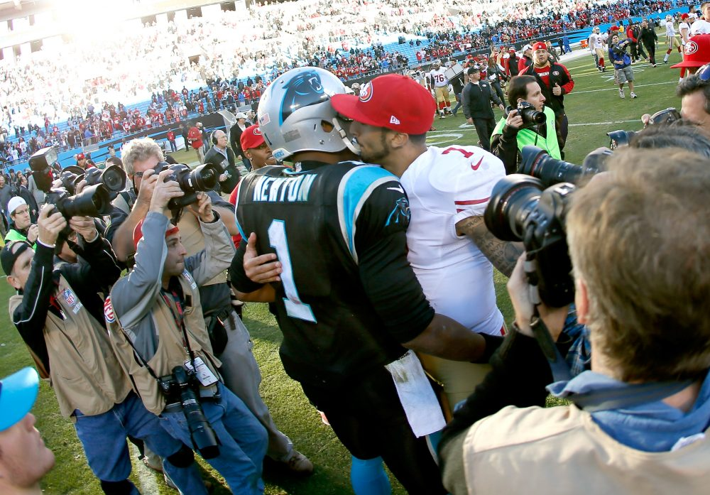 Cam Newton of the Carolina Panthers and former 49ers quarterback Colin Kaepernick speak after their 2014 NFC Divisional Playoff Game. If Kaepernick becomes part owner of the Panthers, he'll be Newton's boss. (Kevin C. Cox/Getty Images)