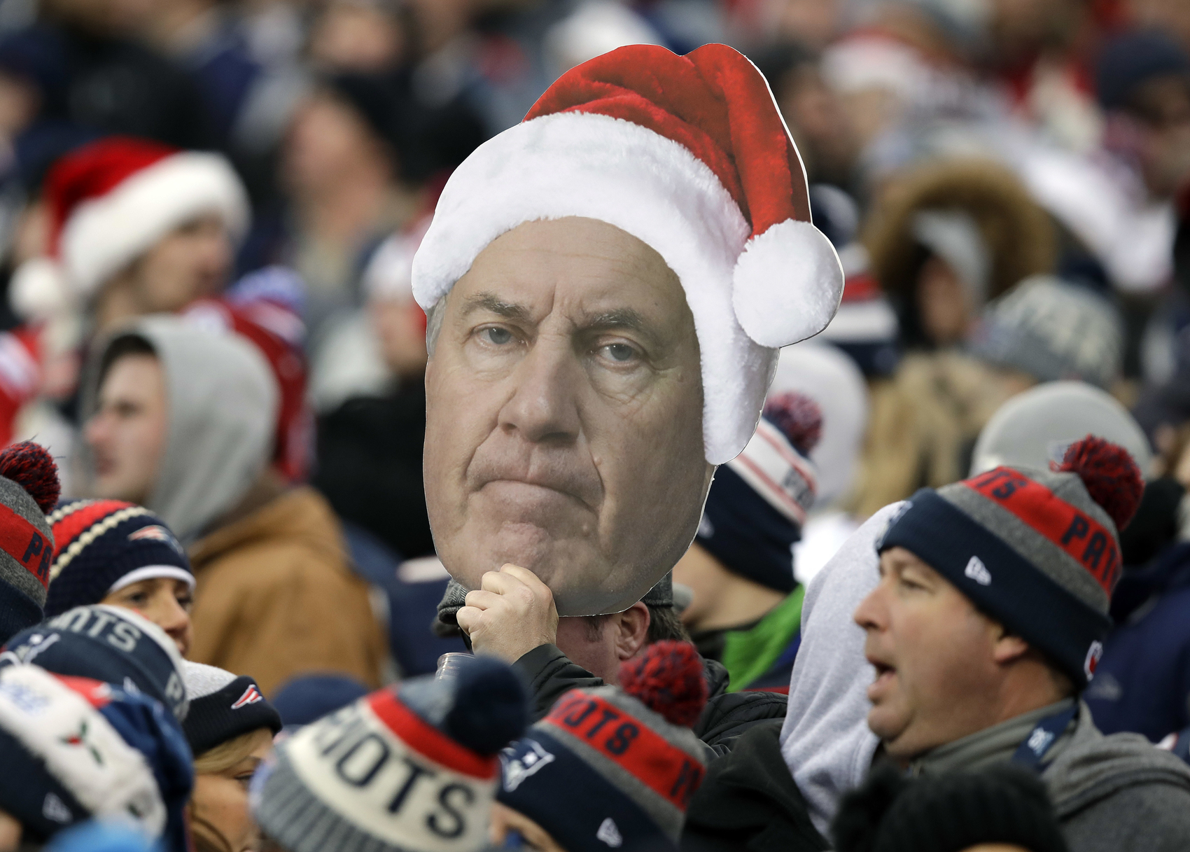 A fan holds a photo of New England Patriots head coach Bill Belichick wearing a Christmas hat during the second half of an NFL football game between the Patriots and the Buffalo Bills, Sunday, Dec. 24, 2017, in Foxborough, Mass. (AP Photo/Charles Krupa)