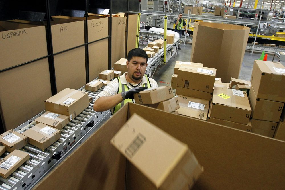 FILE - In this Nov. 11, 2010 file photo, Ricardo Sandoval sorts packages at an Amazon.com fulfillment center, in Phoenix. Merchants are working hard to make same-day delivery a reality, particularly in major cities, from Amazon testing deliveries via taxis to everyone from Target to Google expanding their same-day delivery services. (AP Photo/Ross D. Franklin, File)