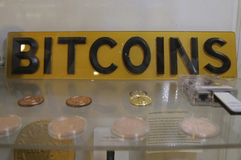In this Friday, Dec. 8, 2017, photo, coins and sign are displayed next to a Bitcoin ATM in Hong Kong. The launch of a U.S. futures contract for bitcoin on Sunday, Dec. 10, 2017, underscores the virtual currency's increasing mainstream acceptance, including in many parts of Asia, where it already has a wide following among speculators and investors. (AP Photo/Kin Cheung)