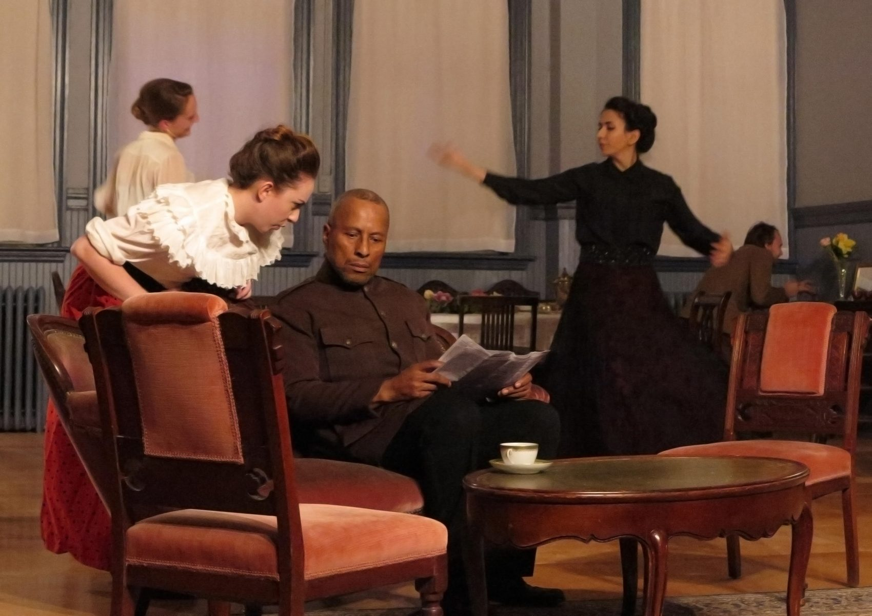 "In the foreground, Olivia Dumaine as Natasha and Paul Benford-Bruce as Chebutykin. In the background, Siobhan Carroll as Irina, Deniz Khateri as Masha and  Slava Tchoul as Fedotik US in ""Three Sisters."" (Courtesy Danielle Fauteux Jacques)"