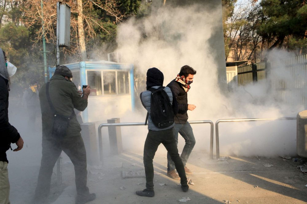 Iranian students run for cover from tear gas at the University of Tehran during a demonstration driven by anger over economic problems, in the capital Tehran on Dec. 30, 2017. (STR/AFP/Getty Images)
