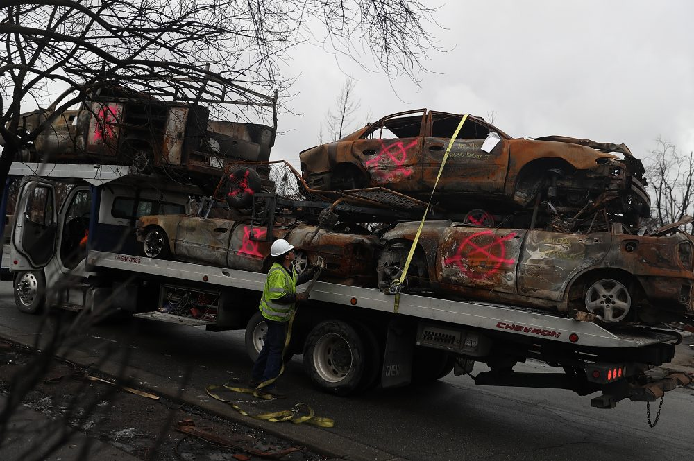A worker secures burned-out cars onto a truck in the Coffey Park neighborhood on Nov. 13, 2017 in Santa Rosa, Calif. (Justin Sullivan/Getty Images)