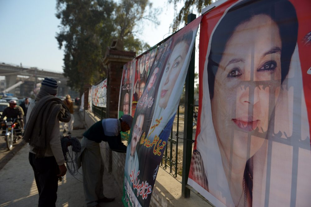 A supporter of the Pakistan Peoples Party (PPP) hangs a poster of slain former Prime Minister Benazir Bhutto at her assassination site in Rawalpindi on Dece. 26, 2014, on the seventh anniversary of her death. (Farooq Naeem/AFP/Getty Images)