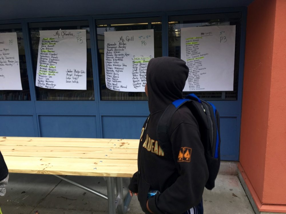 Naseem Bennett, 10, finds his name on the wall on his first day of 5th grade at Oakland's Emerson Elementary School. Naseem and his mom lost their housing in North Oakland last year and he had to commute across three counties so he could maintain some educational stability. It's his legal right. (Lee Romney)