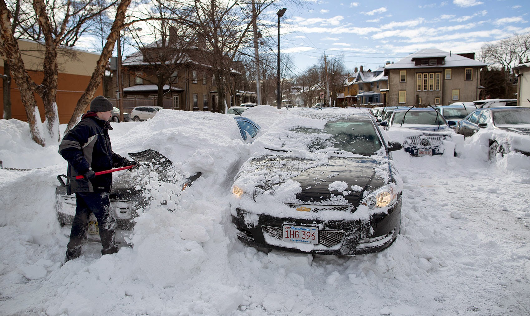 A Boston-area resident digs out their car after a big snowstorm in 2015. (Robin Lubbock/WBUR)