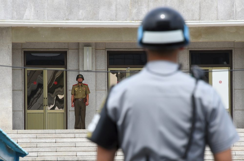 A North Korean soldier (left) looks at the south side as a South Korean soldier (right) stands guard during a press tour to the truce village of Panmunjom in the Demilitarized Zone on July 19, 2017. (Jung Yeon-Je/AFP/Getty Images)