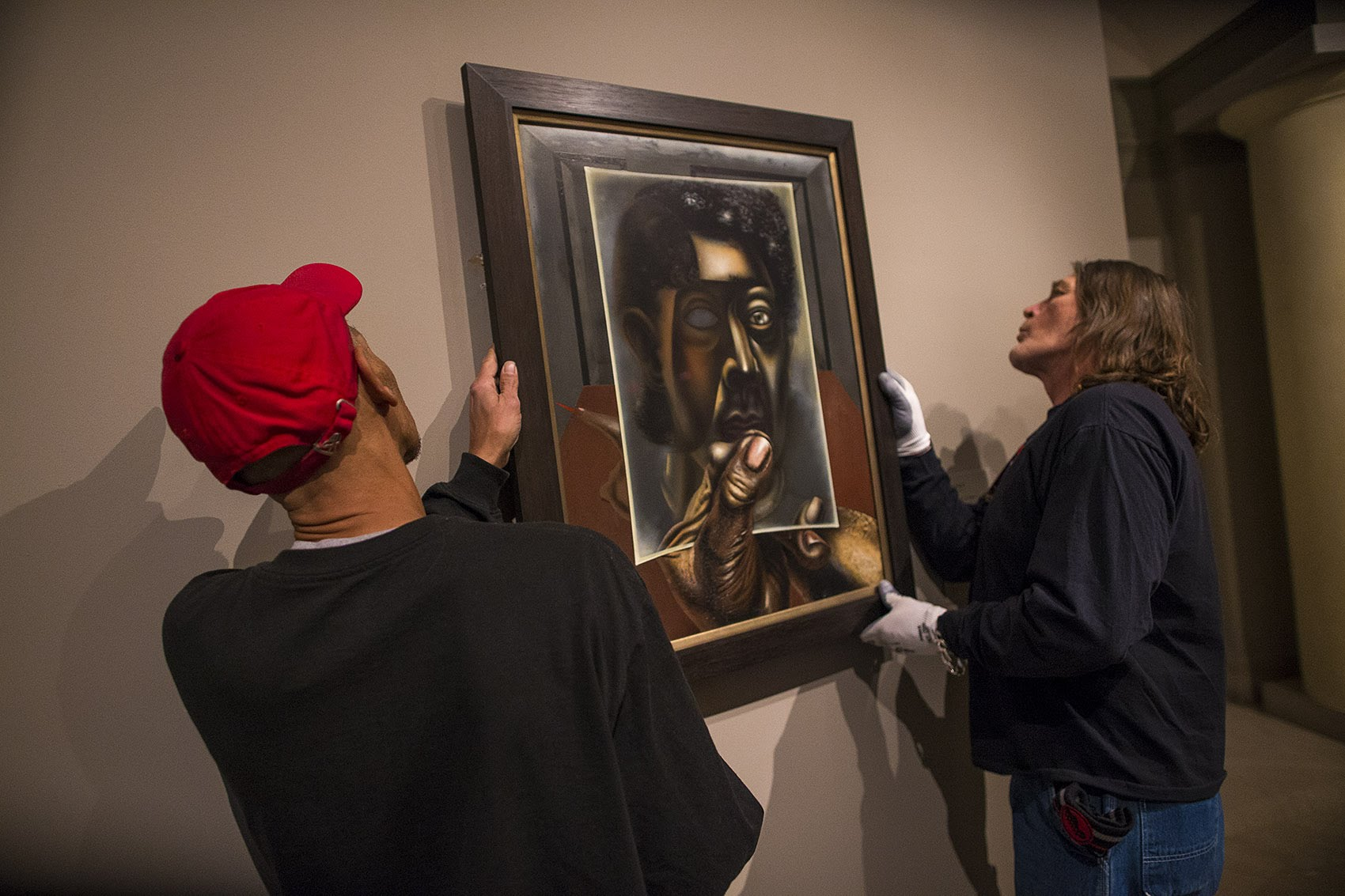 "Museum of Fine Arts facilities workers Bryan Campbell and Paul Picardi install ""Autorretrato con Espejo (Self-Portrait with Mirror)"" by David Alfaro Siqueiros. (Jesse Costa/WBUR)"