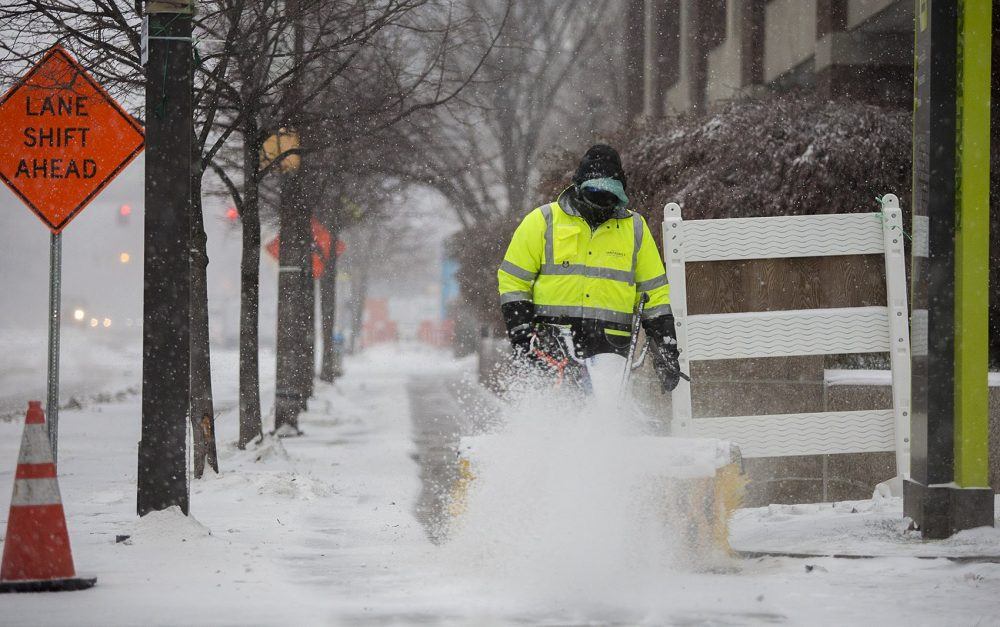 A man sweeping snow off the sidewalk on Broadway in Kendall Square. (Jesse Costa/WBUR)