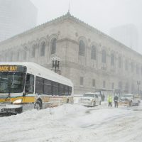 MBTA staff work to move a bus stuck across Boylston Street in front of the Boston Public Library. (Robin Lubbock/WBUR)