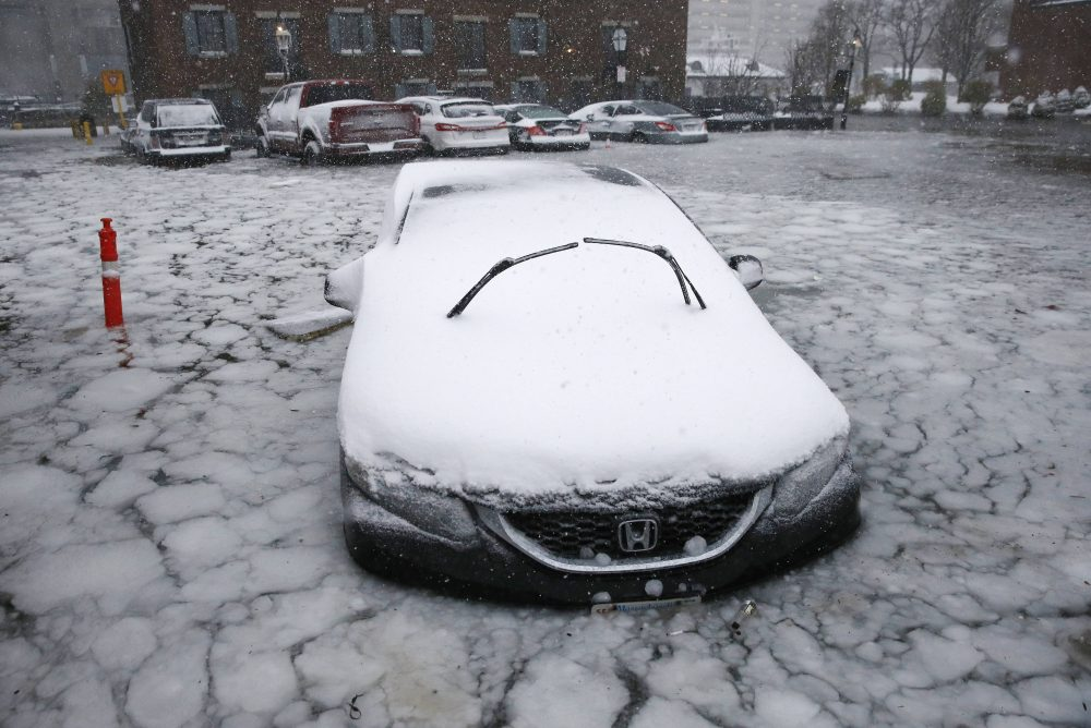 A car sits in floodwaters from Boston Harbor on Long Wharf in Boston.  (Michael Dwyer/AP)