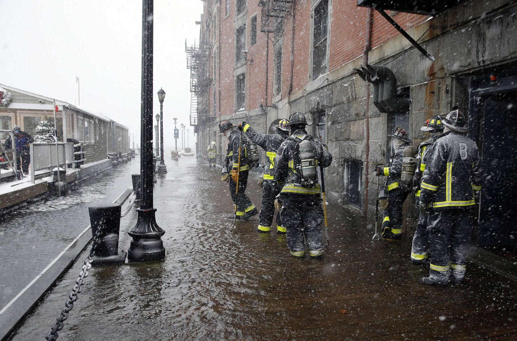 Boston firefighters work at the scene of flooding from Boston Harbor on Long Wharf in Boston, Jan. 4, 2018. (Michael Dwyer/AP)