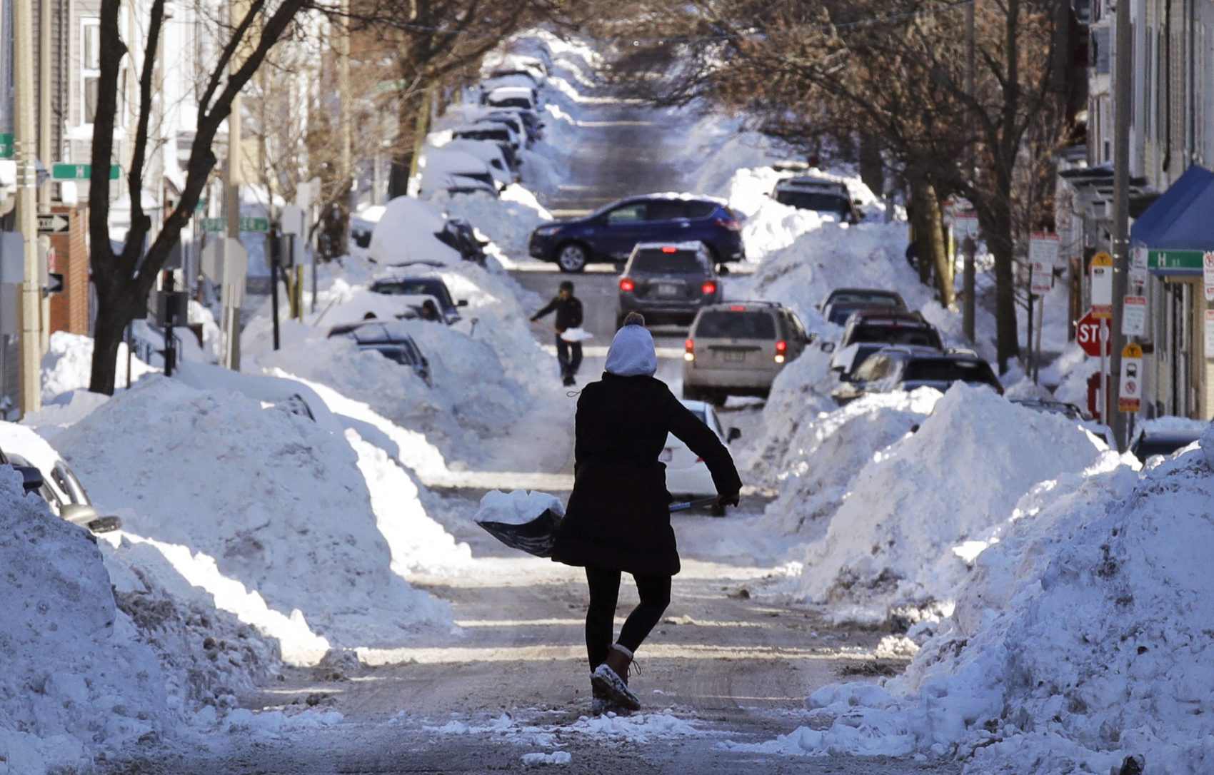 Mollie Lane carries a shovel-full of snow down the street to a pile while digging her car out in the South Boston neighborhood of Boston. (Charles Krupa/AP)