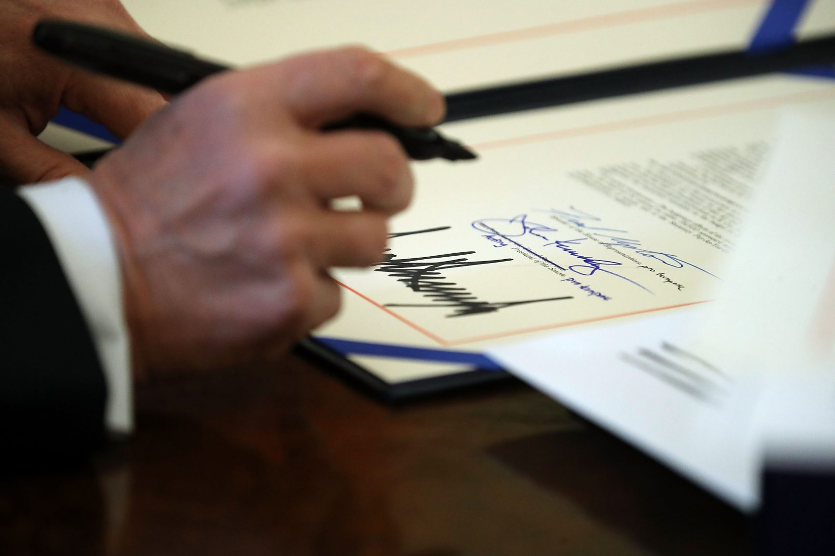 President Trump signs sweeping tax overhaul legislation into law in the Oval Office at the White House, Dec. 22, 2017 in Washington, D.C. (Chip Somodevilla/Getty Images)