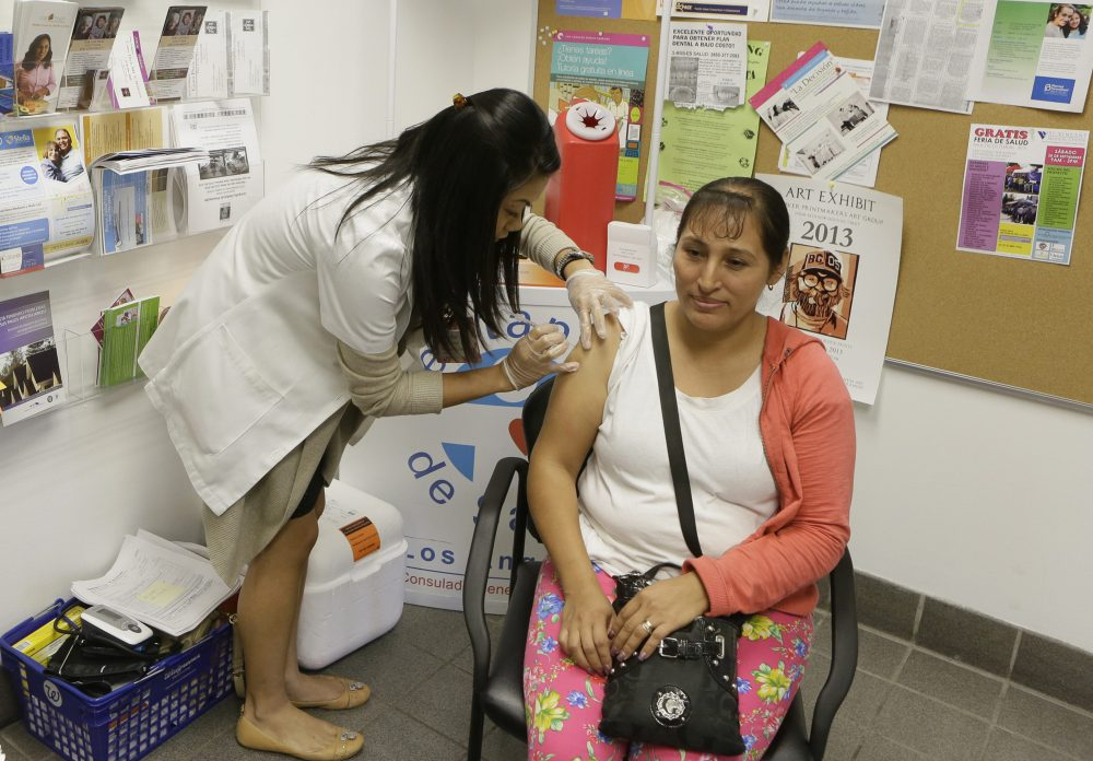 In this Oct. 1, 2013, file photo, Walgreens' pharmacist, Jennifer de Jesus, left, administers a free influenza vaccine to Ana Navarro, 33, during the Binational Health Week event held at the Mexican Consulate in Los Angeles. The flu has hit California so hard this year, pharmacies have run out of medicine to treat it, emergency rooms are packed and the death toll is rising. The Los Angeles Times reports that 27 people younger than 65 have died of the influenza in California since October. (Damian Dovarganes/AP)