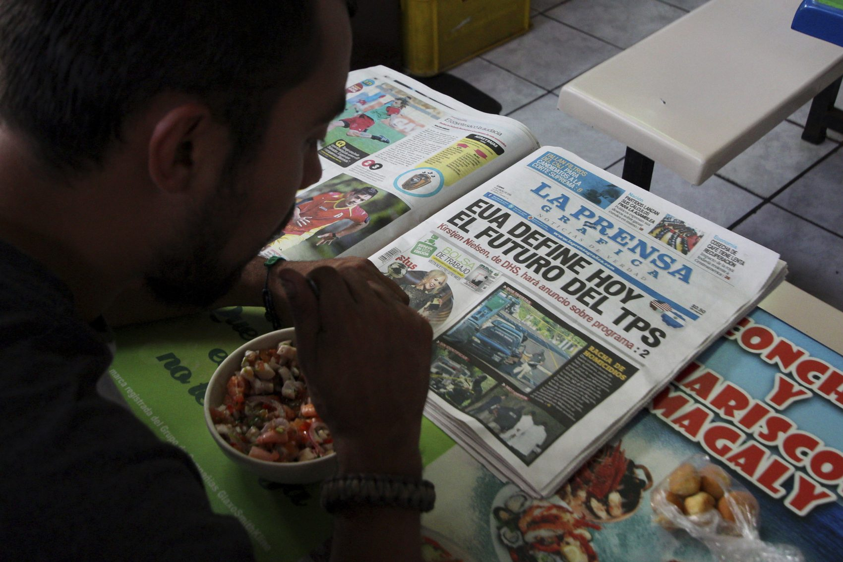 """Mario Escalante reads a newspaper during lunch at a local market in San Salvador, El Salvador, Monday, Jan. 8, 2018. The U.S. administration announced that it will end the temporary protected status that has allowed some 200,000 people from El Salvador to stay legally in the United States for nearly 17 years, the Department of Homeland Security, DHS, said Monday. The newspaper headline reads in Spanish """"The United States will decide today the future of TPS."""" (Salvador Melendez/AP)"""
