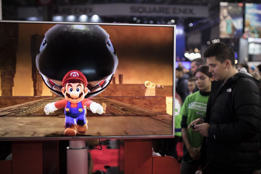 Visitors play Mario Odyssey video game at the Nintendo stand at the Paris Games Week in Paris, Friday, Nov. 3, 2017. (Kamil Zihnioglu/AP)