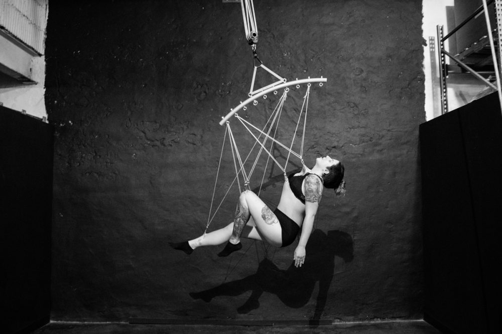 Kirsten Janusewski suspends by hooks in her skin at Skynthesis Body Suspension's studio in Easton, Penn. (Paige Pfleger/WHYY)