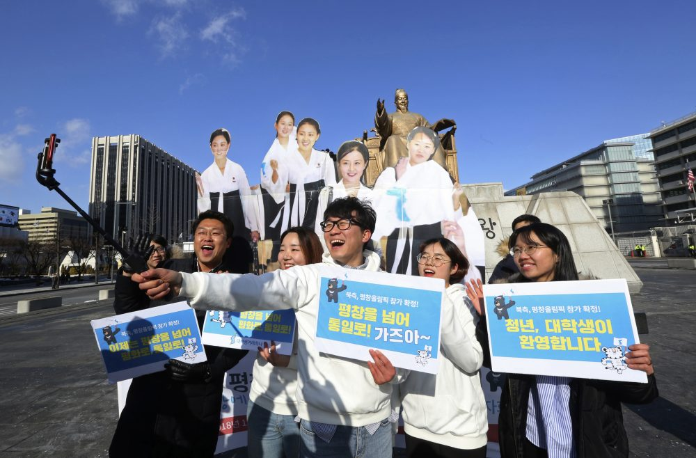 "College students take a selfie with cutouts of North Korean cheerleaders during a rally to welcome the outcome of a meeting between South and North Korea, in Seoul, South Korea, Wednesday, Jan. 10, 2018. South Korea's president said Wednesday he's open to meeting with North Korean leader Kim Jong Un if certain conditions are met, as he vowed to push for more talks and cooperation with the North to try to resolve the nuclear standoff. The letters read: ""We welcome the attendance of North Korea at the Pyeongchang Winter Olympics."" (Ahn Young-joon/AP)"