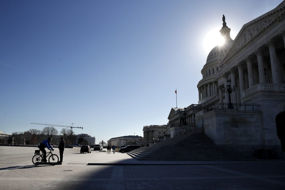 The sun casts a shadow over the Capitol on Friday as a bitterly-divided Congress hurtles toward a government shutdown this weekend. (Jacquelyn Martin/AP)