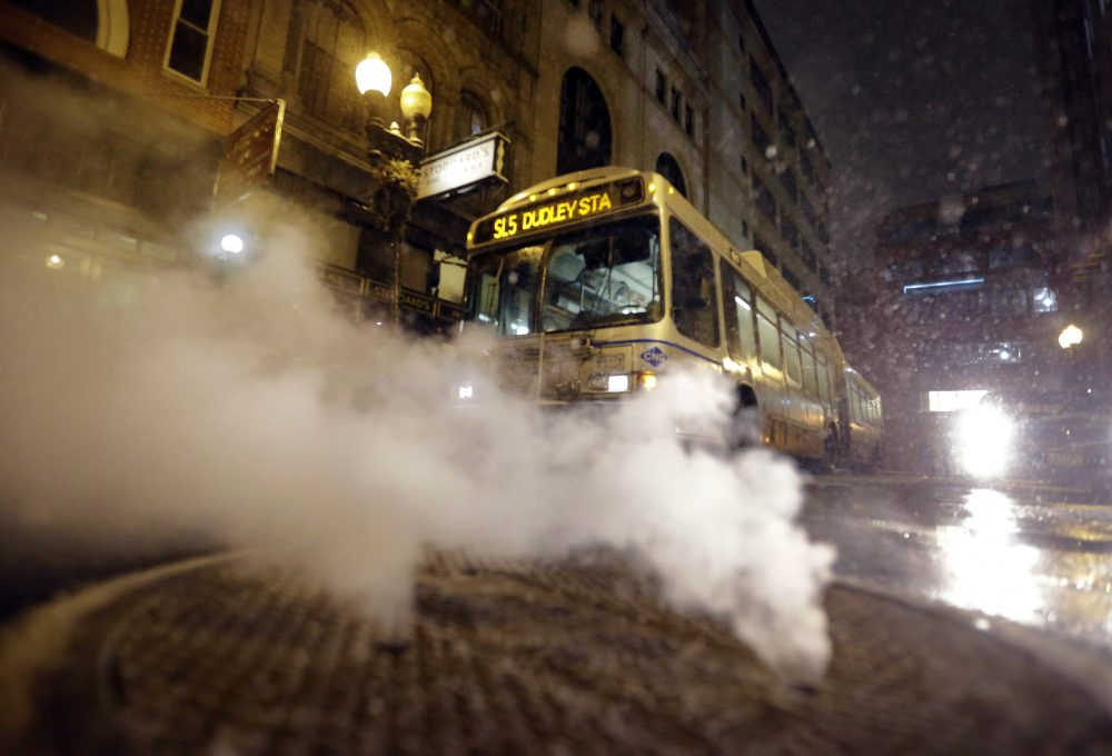 With a bus in the background, steam pours from a manhole cover in January 2015 in Boston. (Steven Senne/AP)