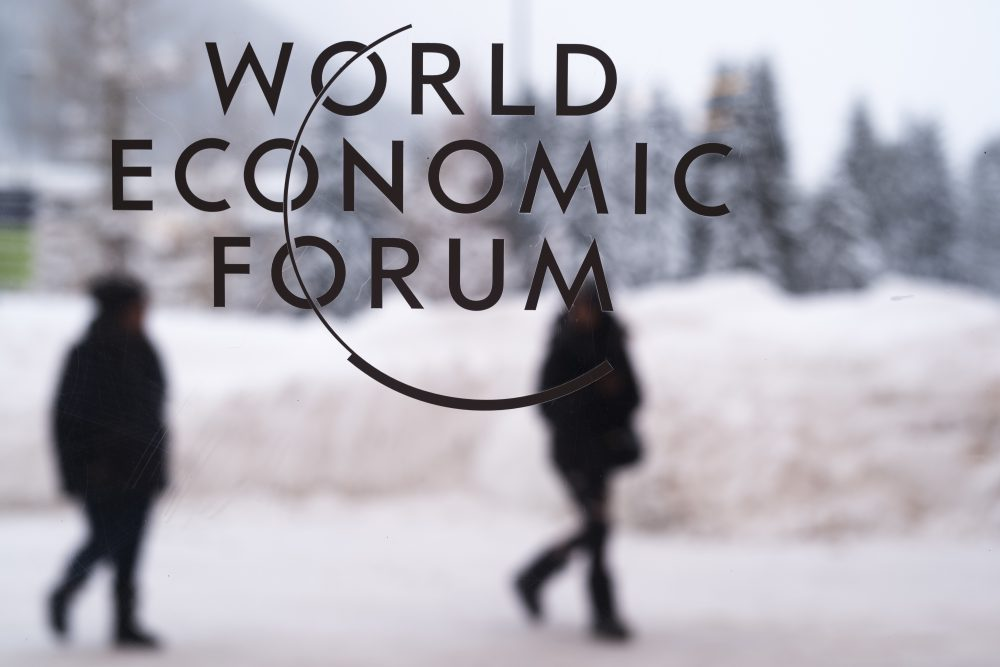 Two people walk behind the logo of the World Economic Forum at the meeting's conference center in Davos, Switzerland, Sunday, Jan. 21, 2018. The meeting brings together entrepreneurs, scientists, chief executives and political leaders from Jan. 23 to 26. (Markus Schreiber/AP)
