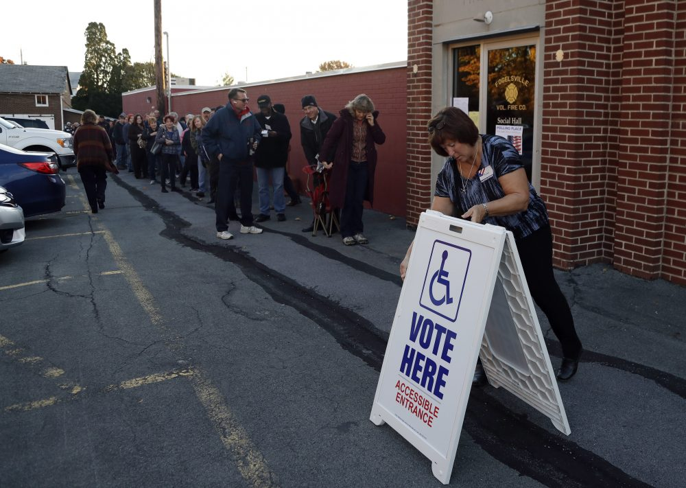 An election official places a sign as voters line up outside a polling place at the Fogelsville Volunteer Fire Co., Tuesday, Nov. 8, 2016, in Fogelsville, Pa. (Matt Slocum/AP)