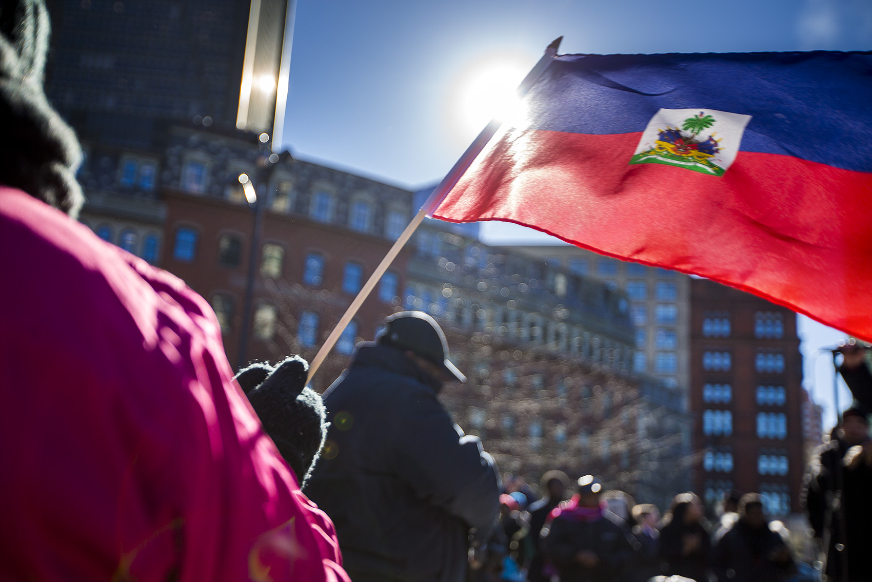 A woman waves a Haitian flag during a rally Friday at Boston City Hall denouncing the Trump administration's decision to cancel the Temporary Protected Status program for Haitians and President Trump's alleged insulting remarks about Haiti. (Jesse Costa/WBUR)