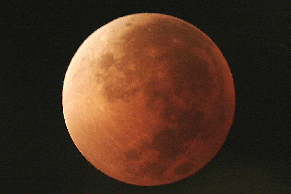 In this Aug. 28, 2007, file photo, the moon takes on different orange tones during a lunar eclipse seen from Mexico City. During a lunar eclipse, the moon's disk can take on a colorful appearance from bright orange to blood red to dark brown and, rarely, very dark gray. On Wednesday, Jan. 31, 2018, a super moon, blue moon and a lunar eclipse will coincide for first time since 1982 and will not occur again until 2037. (Marco Ugarte/AP)