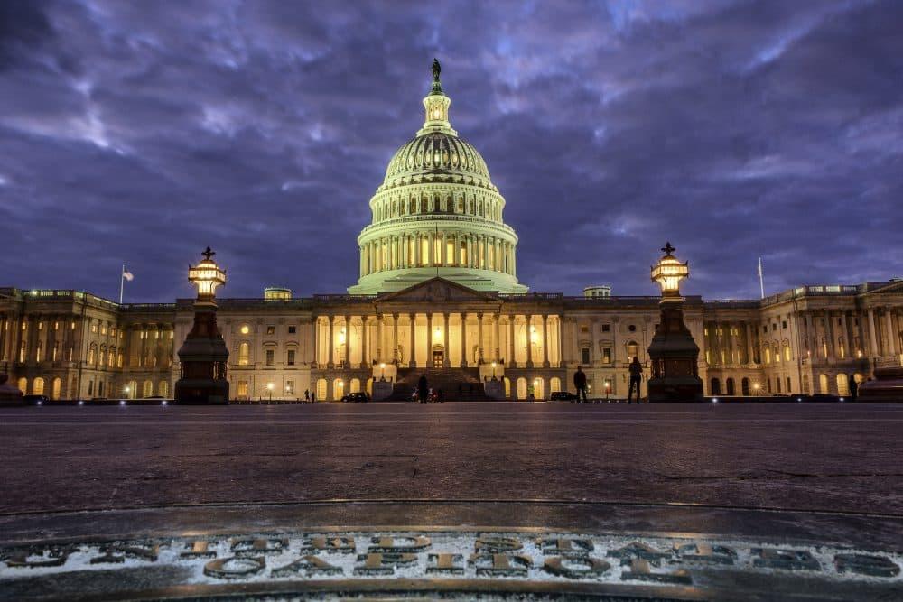 In this Jan. 21, 2018, photo, lights shine inside the U.S. Capitol Building as night falls in Washington. (J. David Ake/AP)