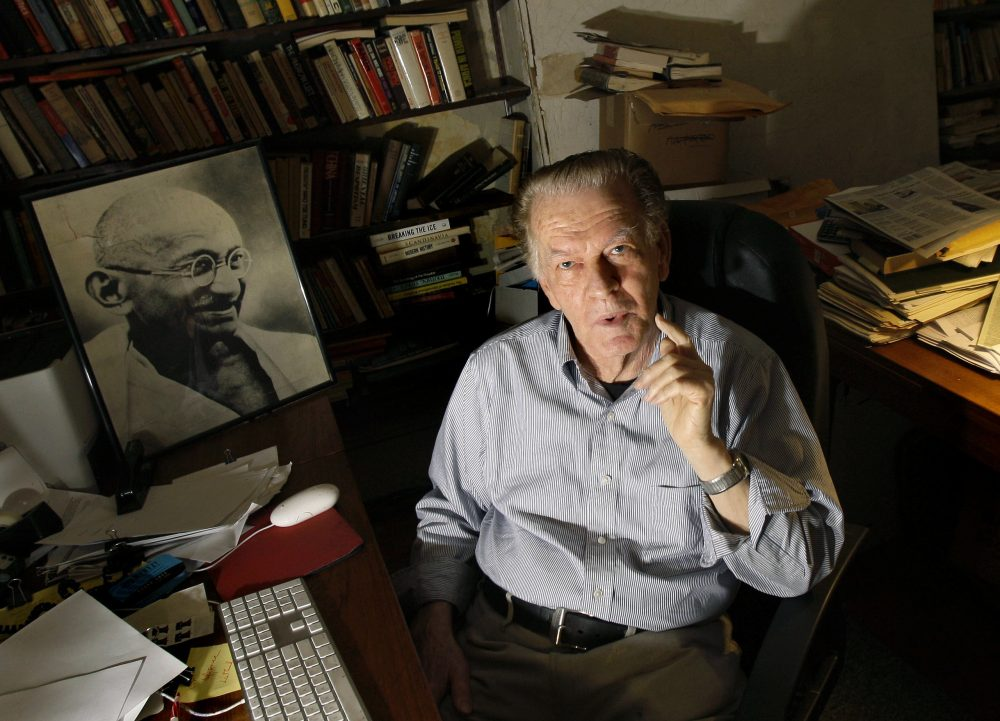 Gene Sharp poses with a photo of Gandhi, left, at his office in Boston in 2009. (Elise Amendola/AP)