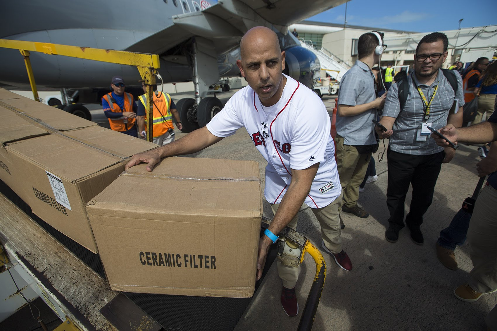 Red Sox manager Alex Cora picks up a box of supplies which will be delivered to his hometown of Caguas, in Puerto Rico. (Jesse Costa/WBUR)