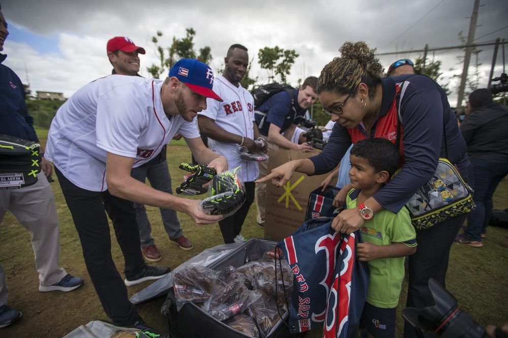Pitcher Chris Sale offers a baseball glove to a young boy while the Red Sox distributed baseball equipment to young children at La Mesa Sports Complex in Caguas. (Jesse Costa/WBUR)