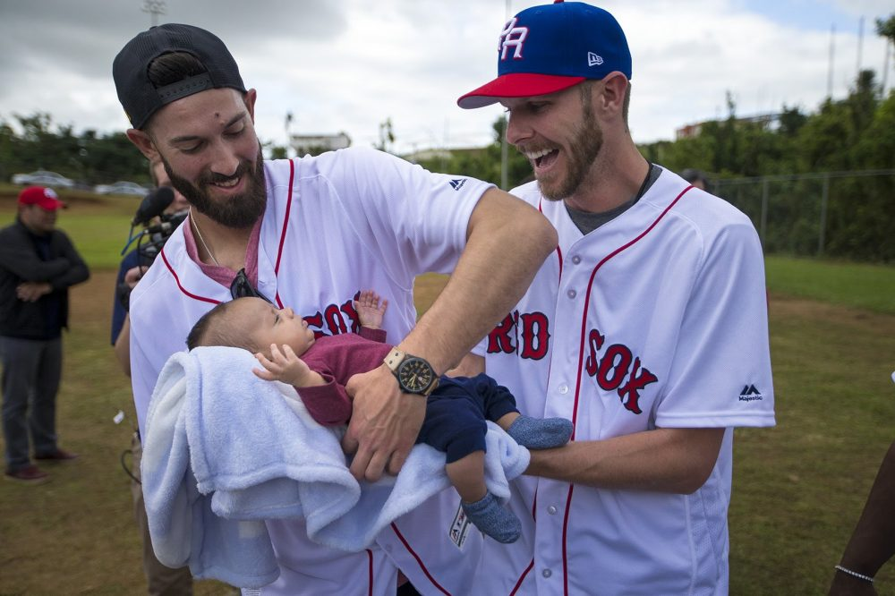 Chris Sale hands baby Alex Valez very carefully over to Rick Porcello. (Jesse Costa/WBUR)