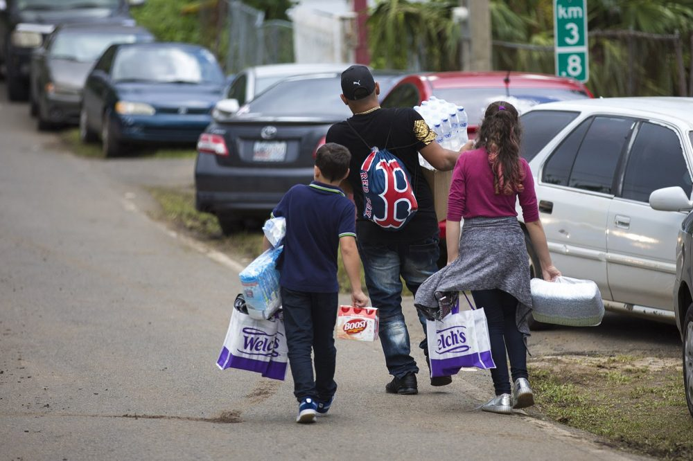 People walk down the road with bags of supplies collected at the Red Sox relief event in Caguas. (Jesse Costa/WBUR)
