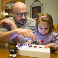 Jake Lacourse and his daughter Rebecca play with the BecDot. (Robin Lubbock/WBUR)