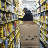 In this 2017 file photo, a clerk reaches to a shelf to pick an item for a customer order at the Amazon Prime warehouse, in New York. (Mark Lennihan/AP)