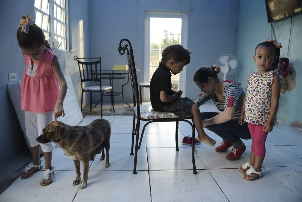 In this Dec. 22, 2017 photo, Wilmarie González Rivera prepares her children to attend a Christmas party at their school in Morovis, Puerto Rico. (Carlos Giusti/AP)