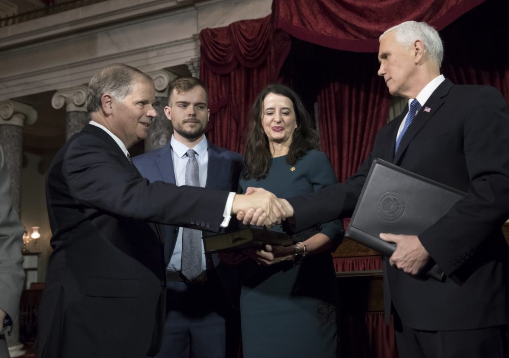 Vice President Mike Pence, right, shakes hands with Sen. Doug Jones, D-Ala., left, after administering the Senate oath of office during a mock swearing in ceremony in the Old Senate Chamber to Jones, with his wife Louise Jones, second from right, Wednesday, Jan. 3, 2018 on Capitol Hill in Washington. (J. Scott Applewhite/AP)