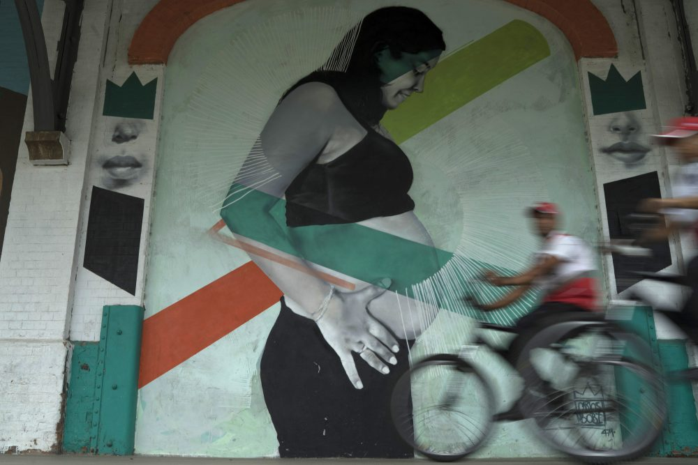 In this Wednesday, Jan. 3, 2018 photo, police officers drive their bicycles past a mural art by Brazilian artist Carlos Bobi in Rio de Janeiro, Brazil. As in many countries, abortion is a subject of taboo in Brazil, a socially conservative nation with the world's largest Roman Catholic population as well as a growing evangelical Christian community. (Leo Correa/AP)