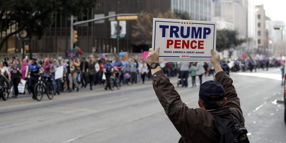A supporter of President Donald Trump holds a sign as a women's march heading to the Texas State Capitol passes on the one-year anniversary of President Donald Trump's inauguration, Saturday, Jan. 20, 2018, in Austin, Texas. (Eric Gay/AP)