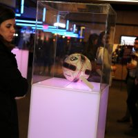 """A visitor looks at a soccer ball in the """"Museum without a Home"""" exhibit. (Courtesy Lisa Aimola/Oxfam)"""