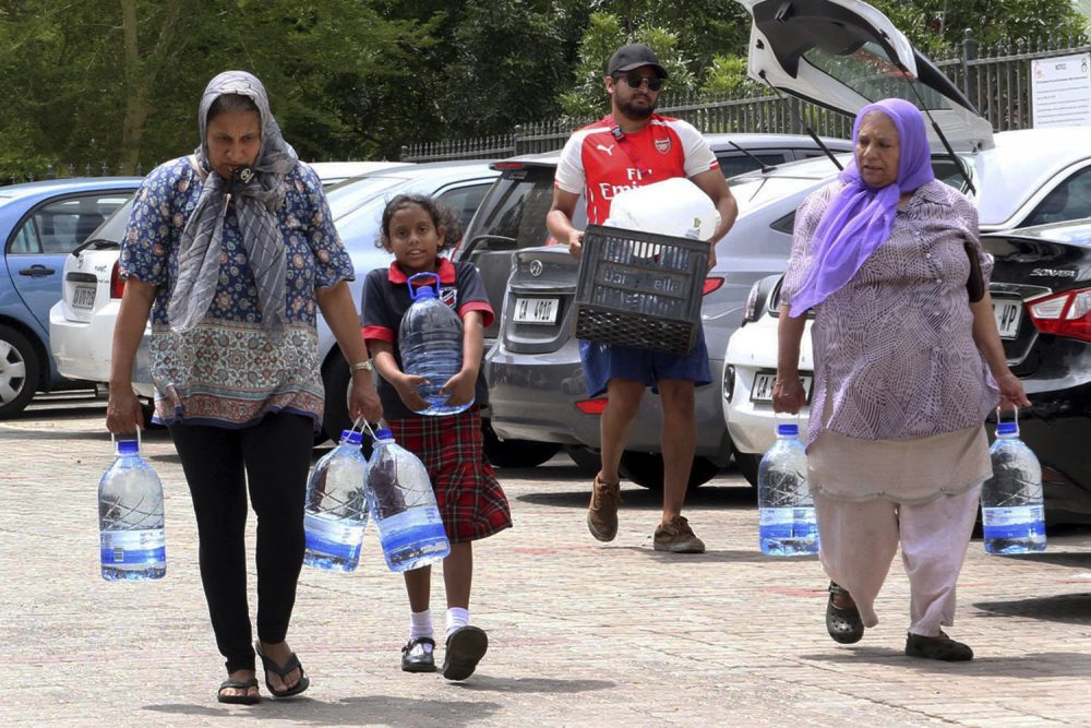 "People carry water collected from a natural spring in Cape Town, South Africa, Monday, Jan 22, 2018 as the city suffers from one of the worst droughts in recent history. Officials are looking to combat the drought, saying it was looking more likely that it will have to turn off most taps on ""Day Zero,"" or April 21 stating that 60 percent of residents are ""callously"" using more than the current limit and that the city will fine households that use too much water. (AP Photo/Anwa Essop)"