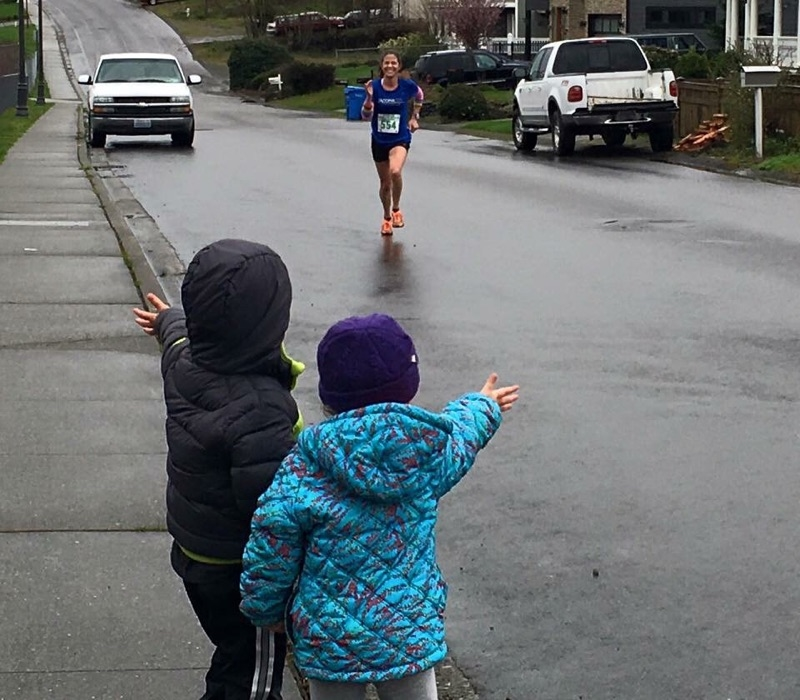 Kate during the 2016 Tacoma St. Patrick's Day Half-Marathon. Her daughter, Grace, and her friend, Charlie, watch along in the foreground. (Courtesy Kate Landau)