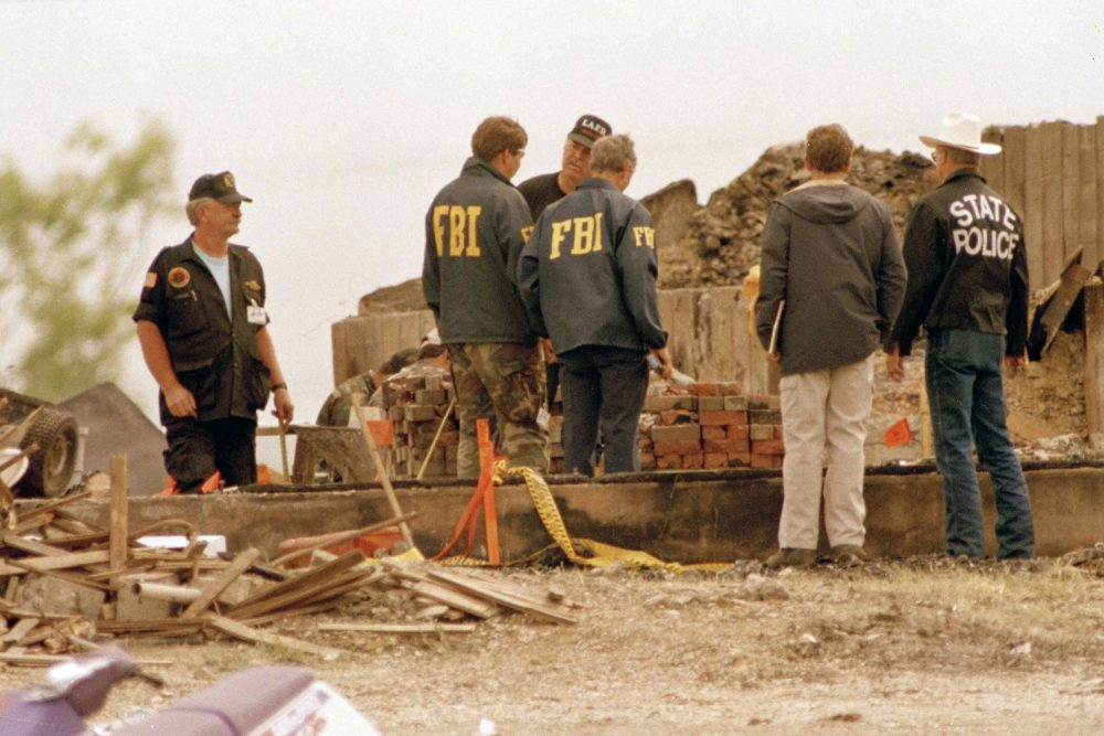 FBI agents, center, confer with another investigator, facing camera, who wears a Los Angeles Fire Department cap, at the site of the destroyed Branch Davidian compound near Waco, April 27, 1993. Lawyers for some of the Branch Davidians questioned the impartiality of an outside team of investigators that concluded the cultists themselves set the fire that destroyed the compound. (AP Photo/Ron Heflin)