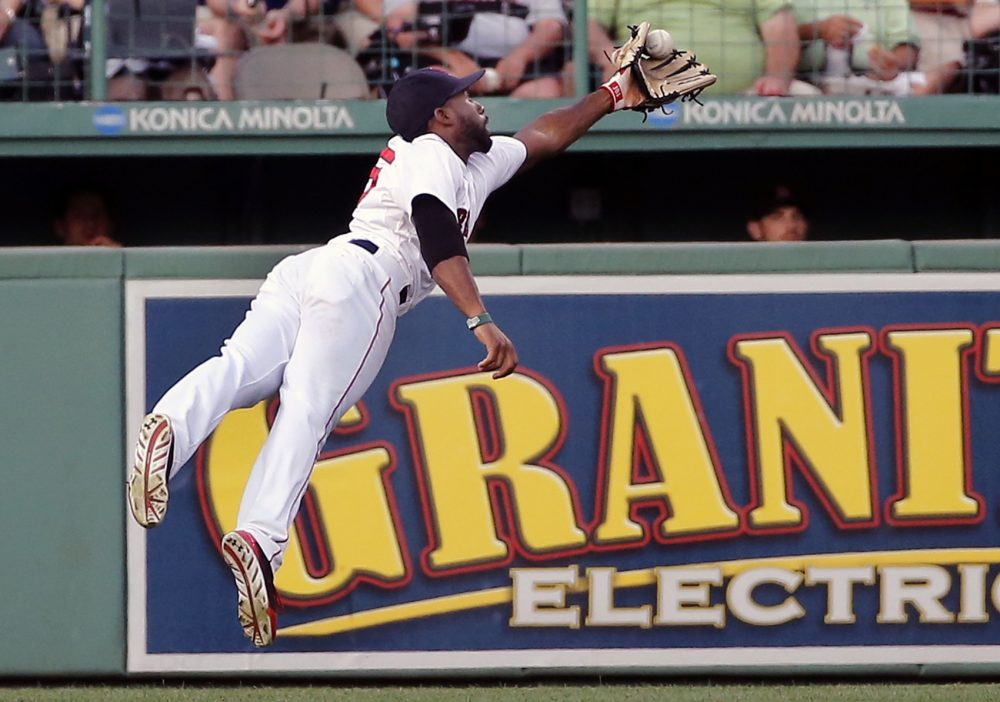 Boston Red Sox center fielder Jackie Bradley Jr. leaps to grab a deep fly by Chicago White Sox's Tyler Flowers in the second inning of a baseball game at Fenway Park in Boston, Wednesday, July 9, 2014. (AP Photo/Elise Amendola)