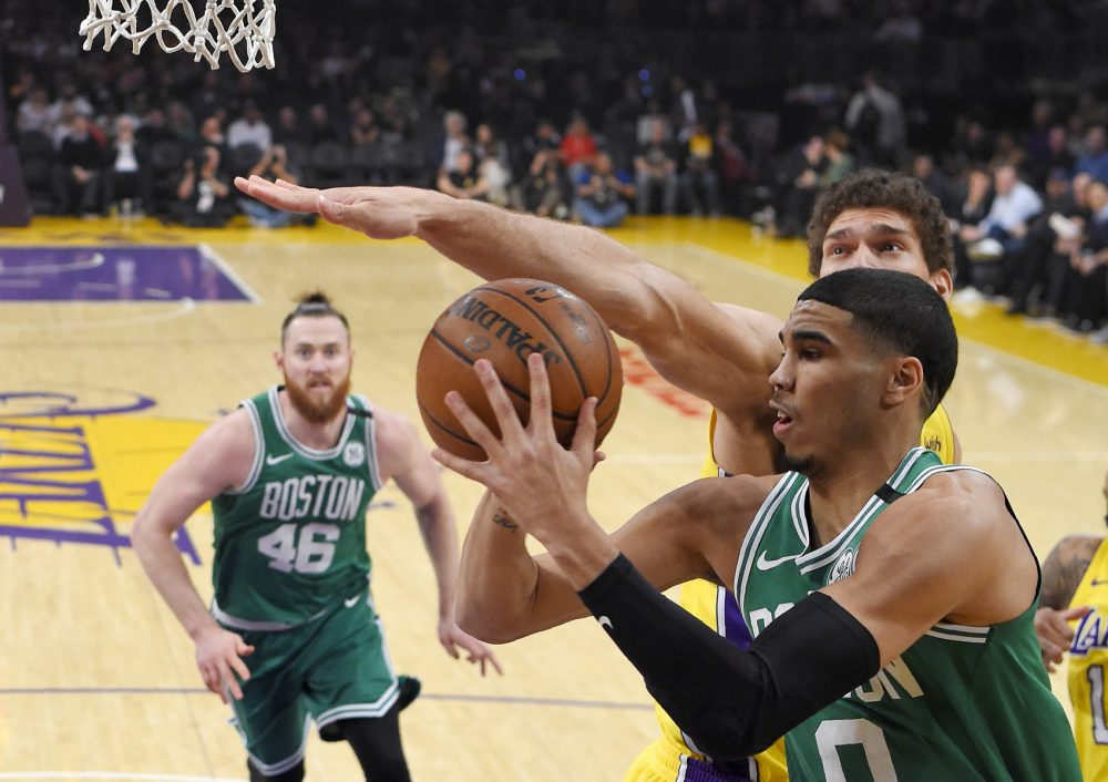 Boston Celtics forward Jayson Tatum, right, passes the ball as Los Angeles Lakers center Brook Lopez, behind, defends and center Aron Baynes, of Australia, watches during the first half of an NBA basketball game Tuesday, Jan. 23, 2018, in Los Angeles. (AP Photo/Mark J. Terrill)
