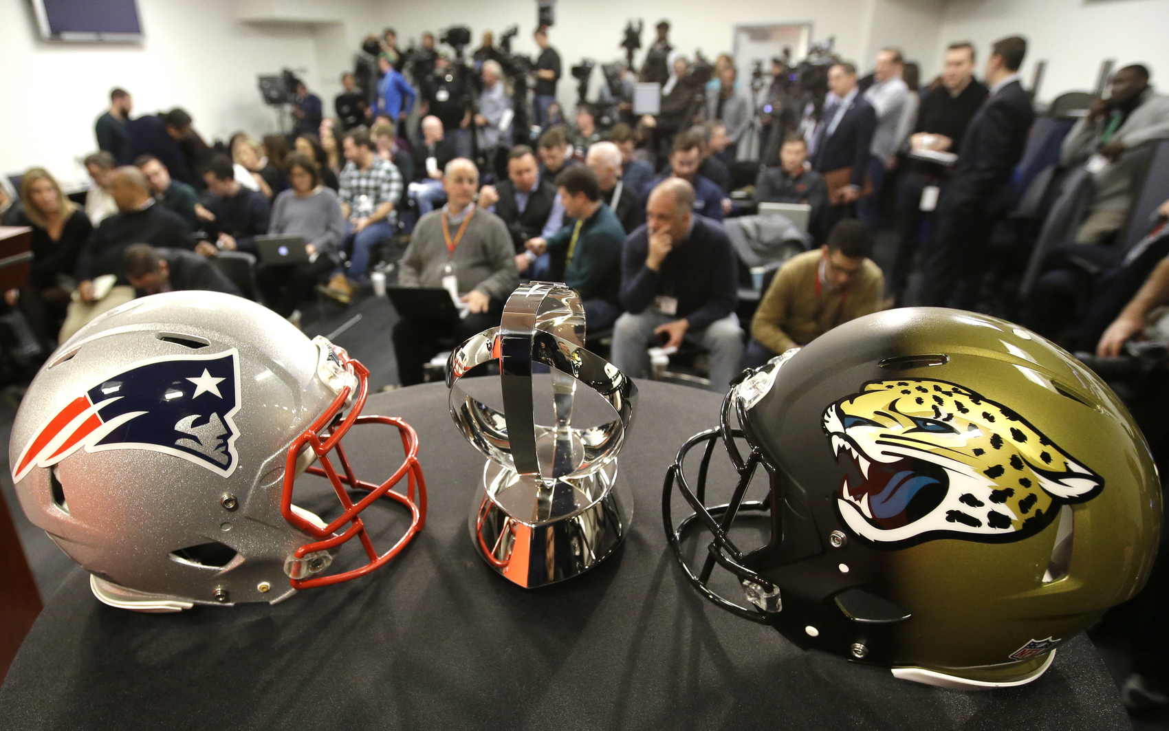 A New England Patriots helmet, left, a Lamar Hunt AFC Championship trophy, center, and a Jacksonville Jaguars helmet, right, are displayed on a podium in front of members of the media, behind, before the start of an NFL football news conference, Wednesday, Jan. 17, 2018, at Gillette Stadium, in Foxborough, Mass. The New England Patriots host the Jacksonville Jaguars in the AFC championship on Sunday (AP Photo/Steven Senne)